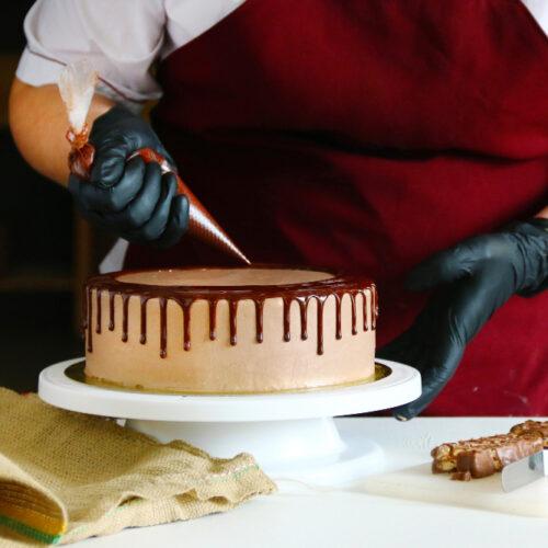 confectioner-squeezes-liquid-chocolate-from-pastry-bag-cream-biscuit-cake